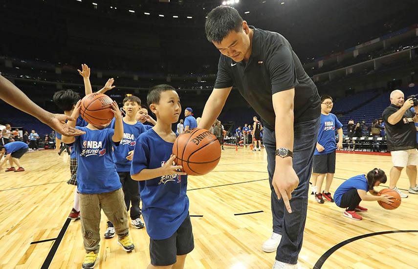 Yao Ming, exbaloncestista chino que jugó 8 temporadas en la NBA, en los Houston Rockets, junto a un grupo de niños chinos. (www.nba.com)